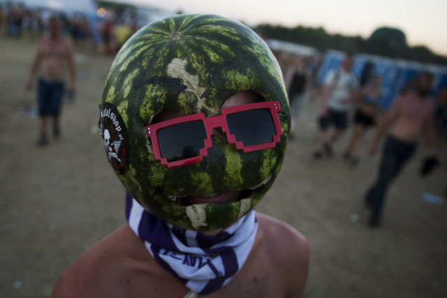 A man wears a mask made of a watermelon at the Woodstock Festival in Kostrzyn-upon-Odra River, close to the Polish-German border, August 2, 2013. REUTERS/Thomas Peter (POLAND - Tags: ENTERTAINMENT SOCIETY TPX IMAGES OF THE DAY) - RTX128X2