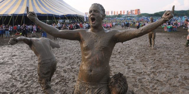 Festival goers covered in mud after a wrestling match during the 2009 Glastonbury Festival at Worthy Farm in Pilton, Somerset.